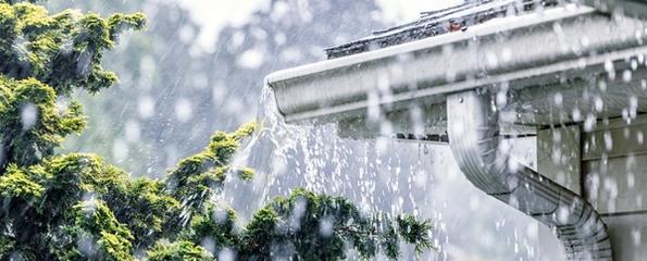 Vann som fosser ut av en takrenne i en regnstorm