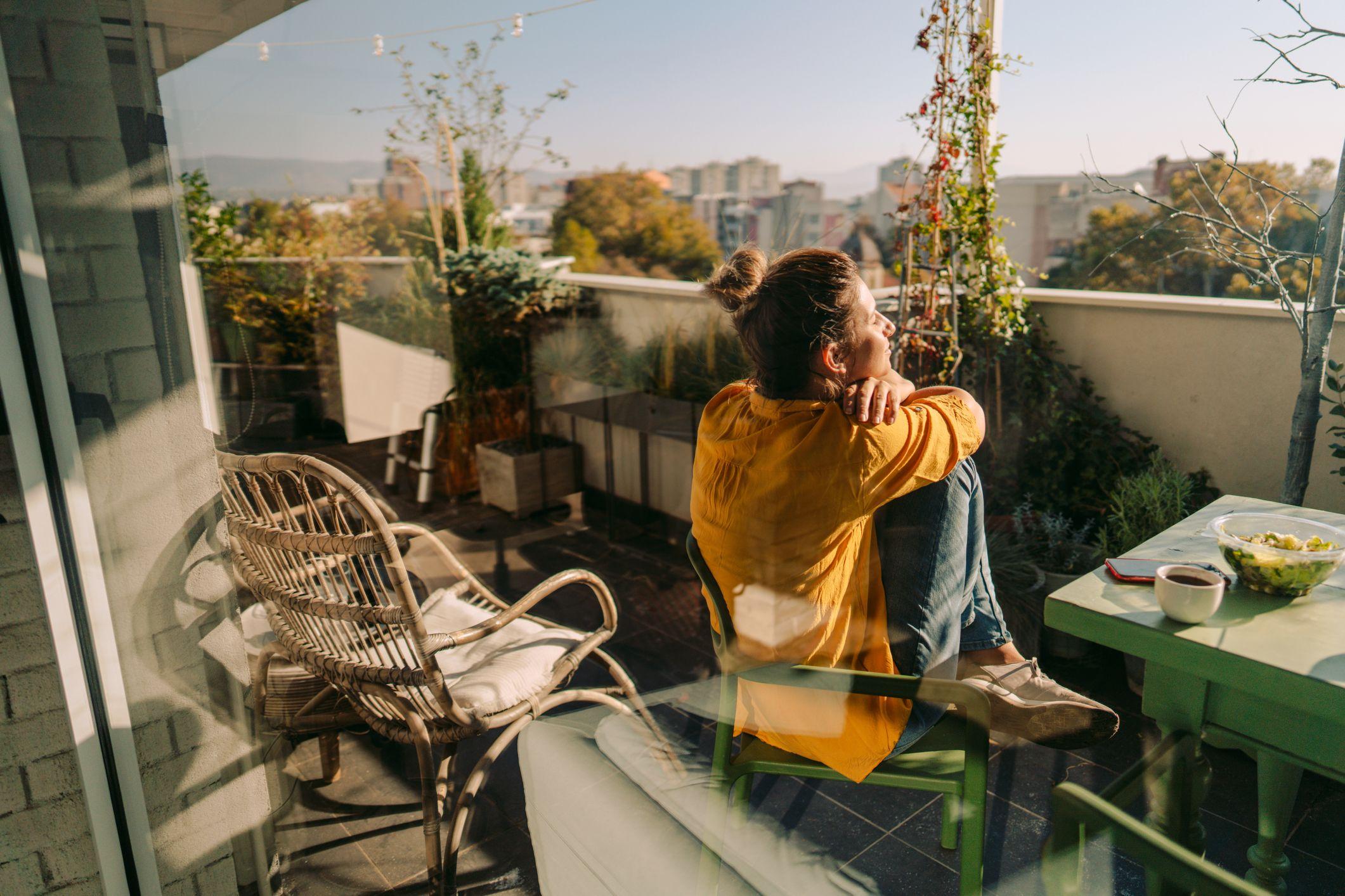 Dame som nyter sola på en frodig balkong