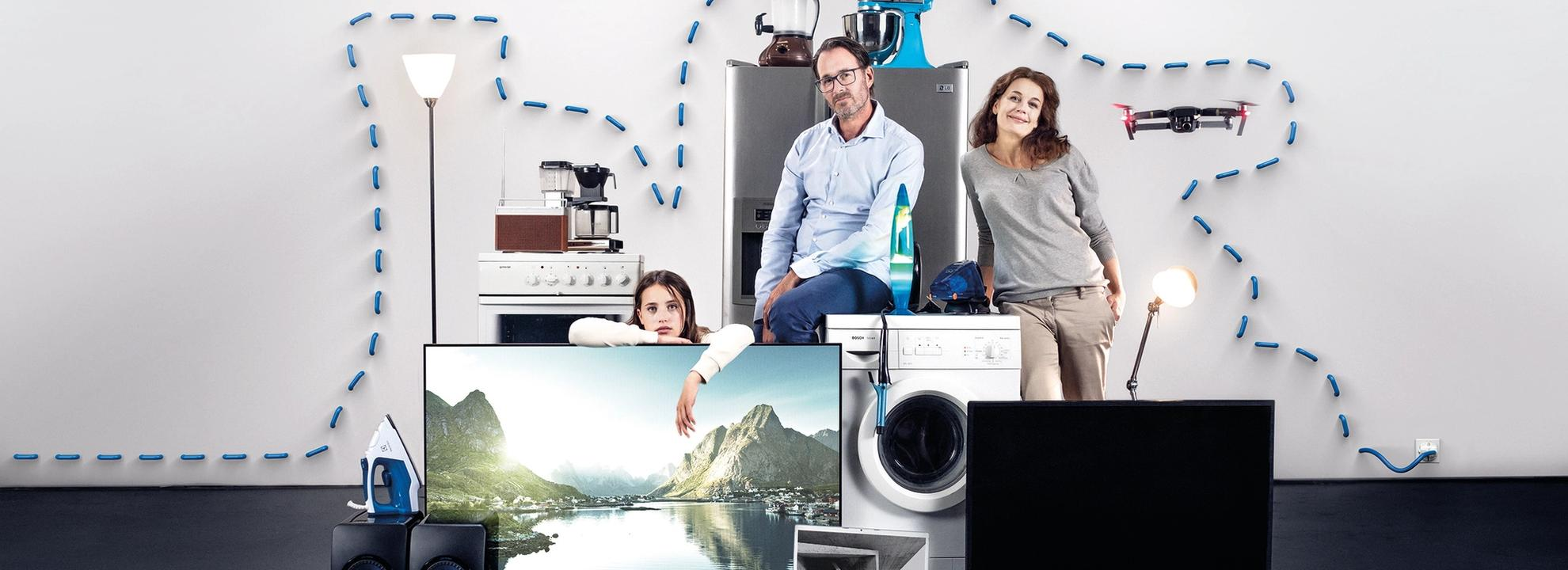 En familie på tre og ulike elektroniske apparater.