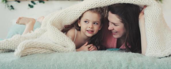 Mor og datter smiler fra under et pledd