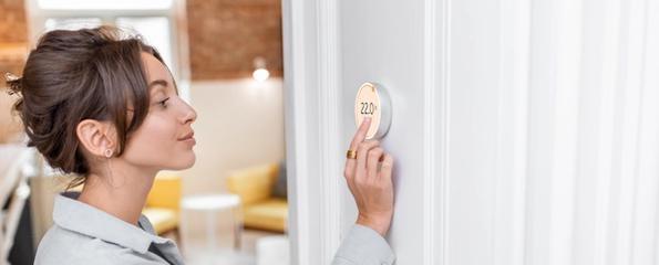 Kvinne som justerer en termostat på veggen