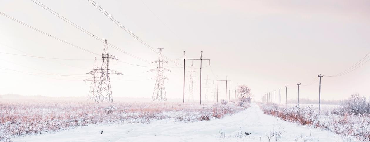 Strømmaster på et snødekt jorde