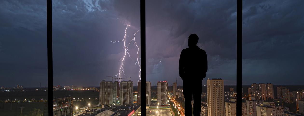 En mann ser ut på lynvær fra leiligheten sin