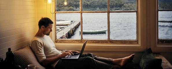 Mann i sofaen med en laptop på hytta med utsikt over sjøen