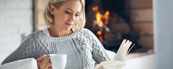 Kvinne som leser en bok foran en peis