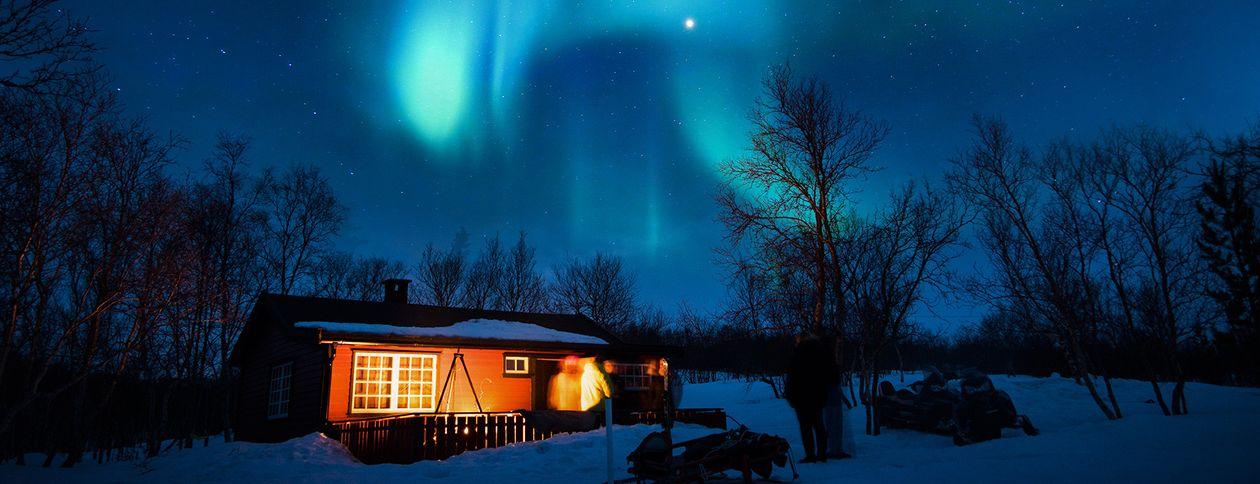 En opplyst hytte i vinterlandskap med nordlys over himmelen