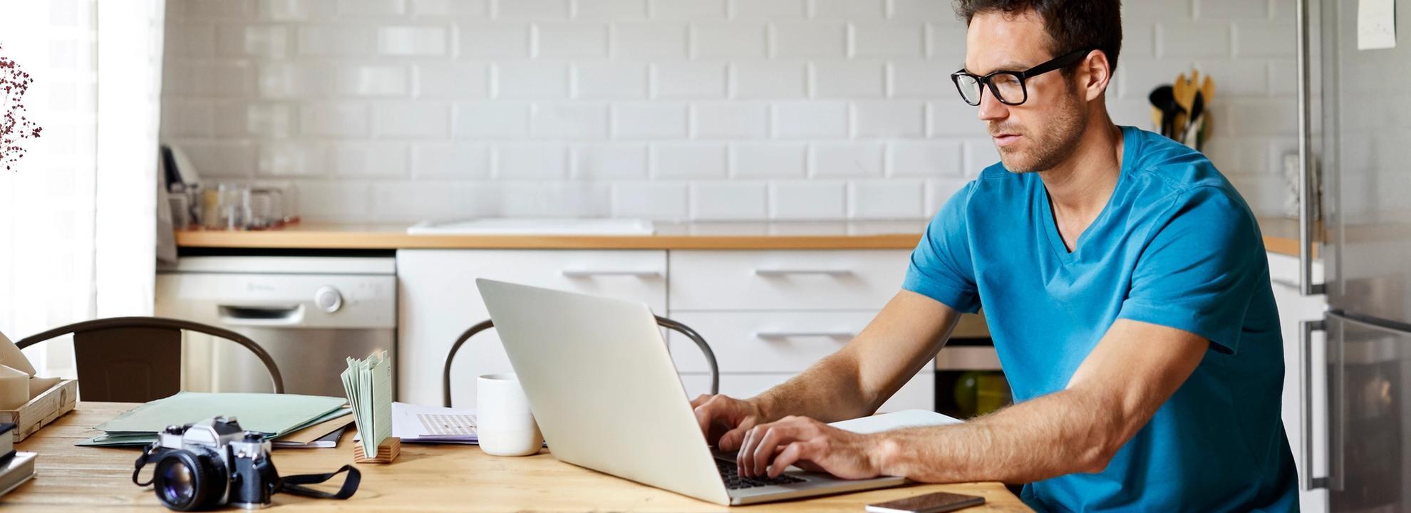 Bilde av mann med PC og kaffekopp.