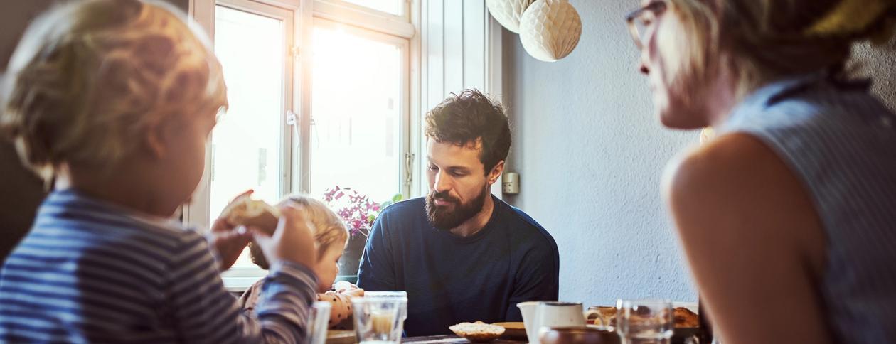 Familie spiser frokost med sollys inn vinduet