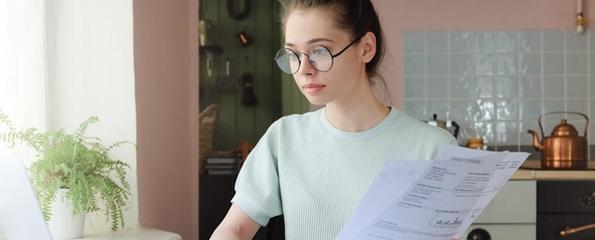 Kvinne sitter med regninger ved en bærbar datamaskin