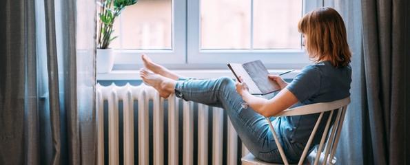 Dame som leser bok ved radiator