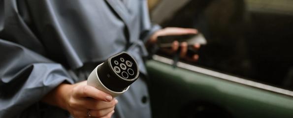 Kvinne med som holder elbil-ladeplugg og mobil
